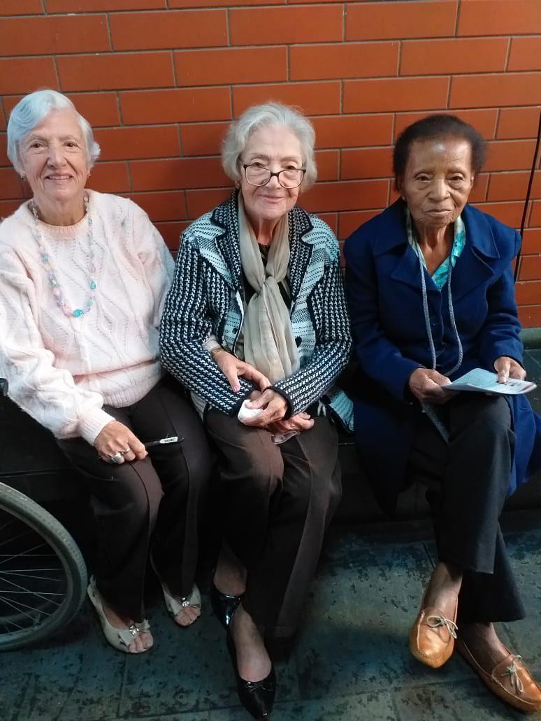 três idosas sentadas banco sorrindo