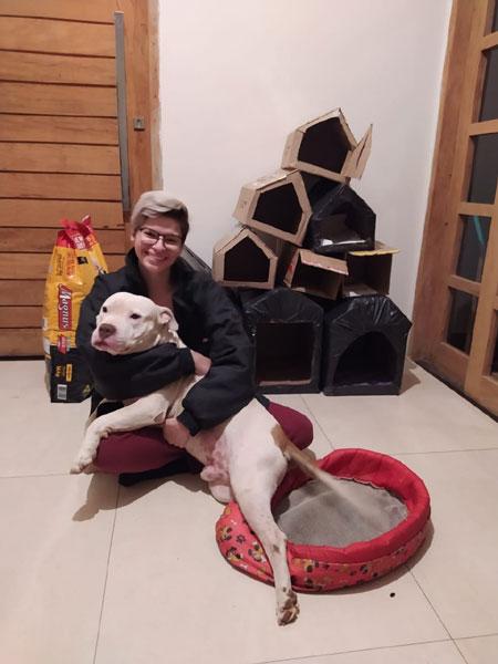 mulher com cachorro no colo, e as casinhas de papelão ao fundo