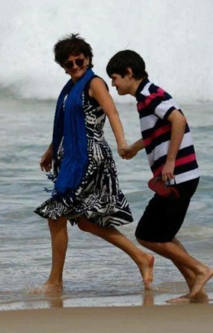 Mãe na praia caminhando de mãos dadas com seu filho autista