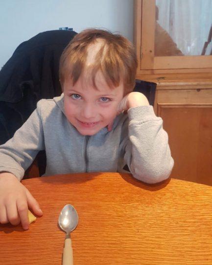 Imagem de menino sorrindo com cabelo cortado no meio sentado em uma mesa com uma colher à sua frente