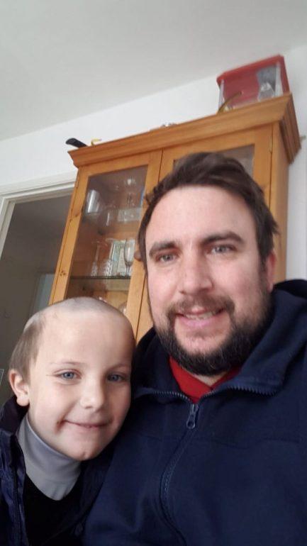 Imagem de homem abraçando filho de 5 anos com o cabelo raspado