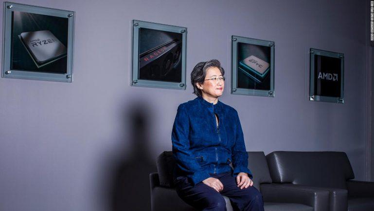 Imagem de mulher sentada em sofá com quadros ao fundo olhando para o horizonte
