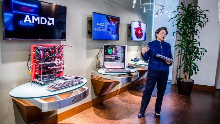 Mulher em frente a computadores mostrando tecnologia desenvolvida por sua empresa
