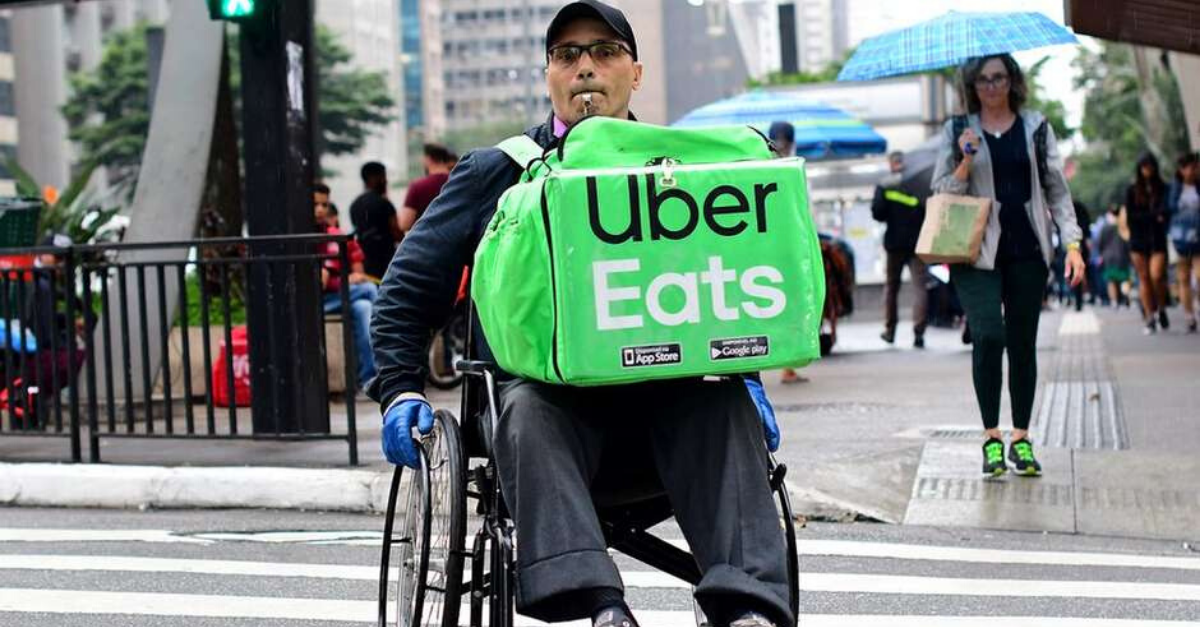 cadeirante carrega mochila uber eats atravessa avenida