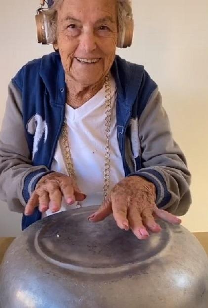 Imagem de idosa gravando vídeo para o TikTok imitando DJ com uma panela