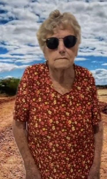 Imagem de idosa com paisagem ao fundo gravando vídeo para o TikTok