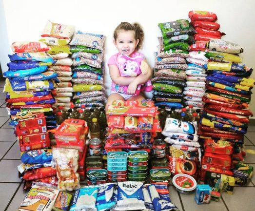 menina sentada sorrindo cercada alimentos ganhou aniversário doar