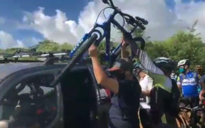 Ciclistas retirando bicicleta de cima de carro