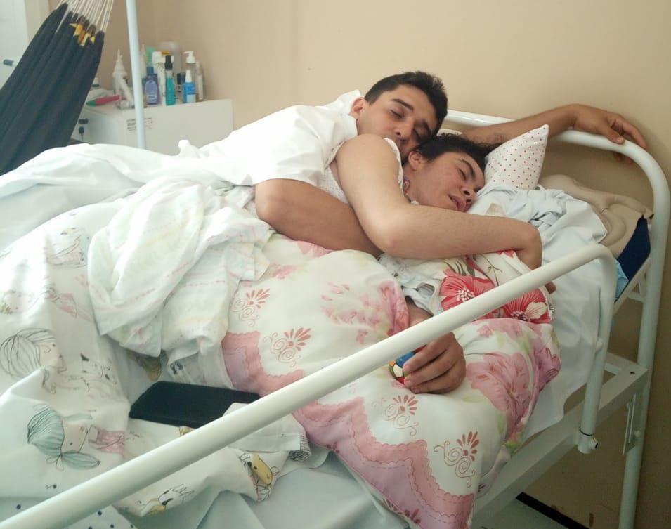 marido deitado abraçado esposa estado vegetativo leito hospital