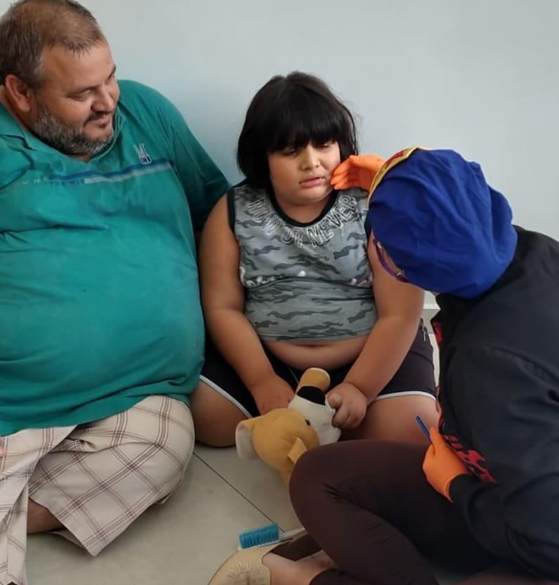 dentista sentada chão passa mão rosto criança
