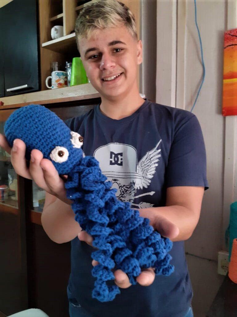 menino mostra polvo crochê azul