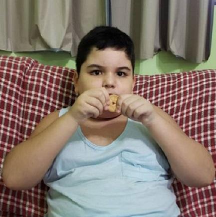 Garoto autista sentado em sofá comendo biscoito de coração
