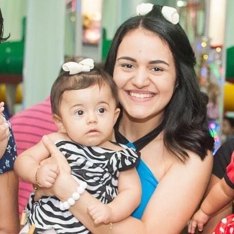 mãe com filha pequena sorrindo festa aniversário