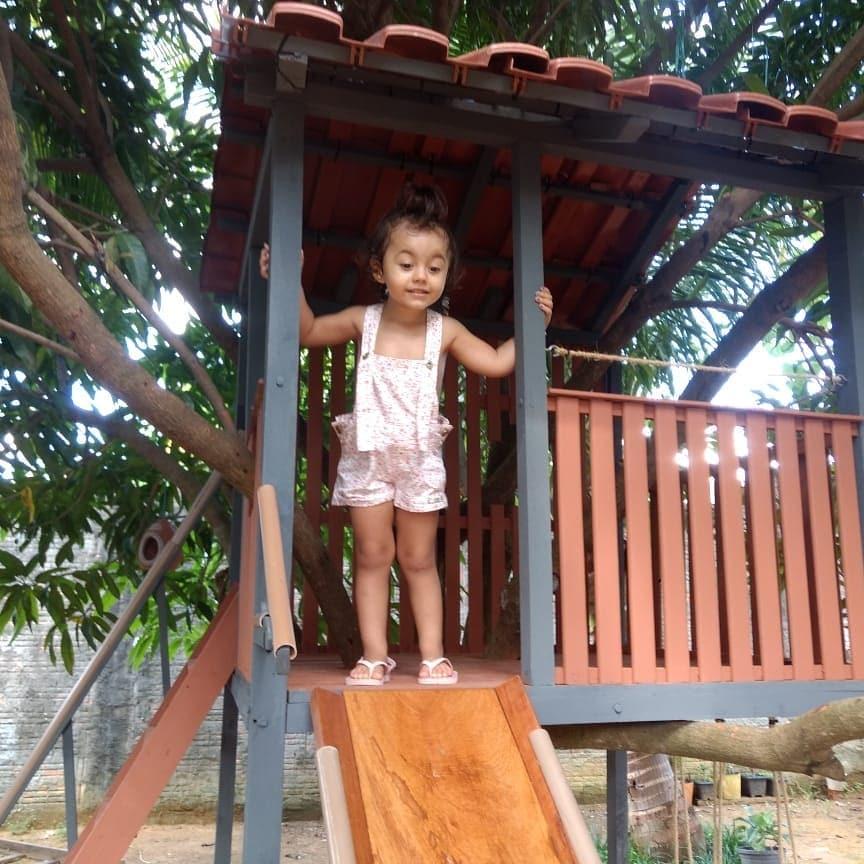 menina casinha na árvore olhando escorregador