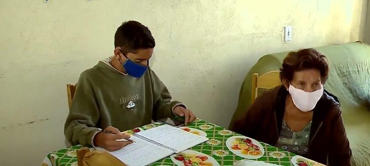menino estudando mesa ao lado avó