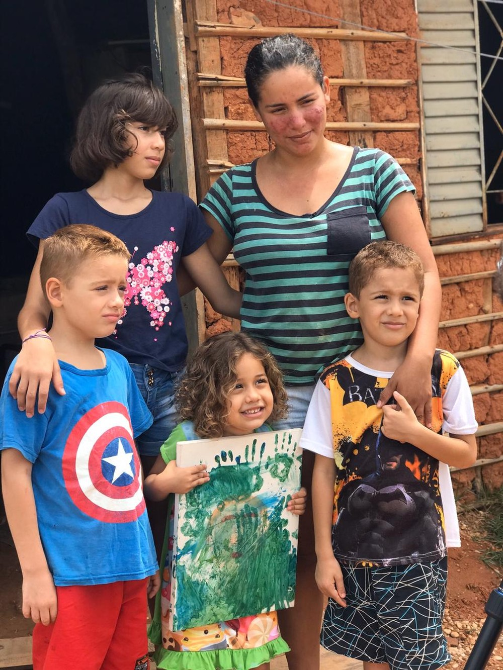 mãe e filhos em frente casa taipa