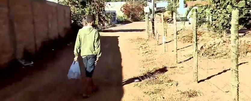 menino carregando sacola latinha terra areia