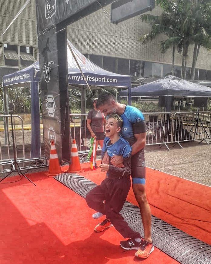 pai carrega filho paralisia cerebral linha chegada prova triatlo