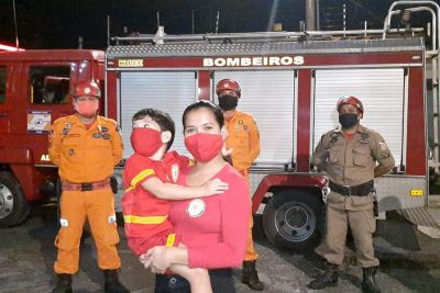 mãe segurando filho colo em frente caminhão bombeiros
