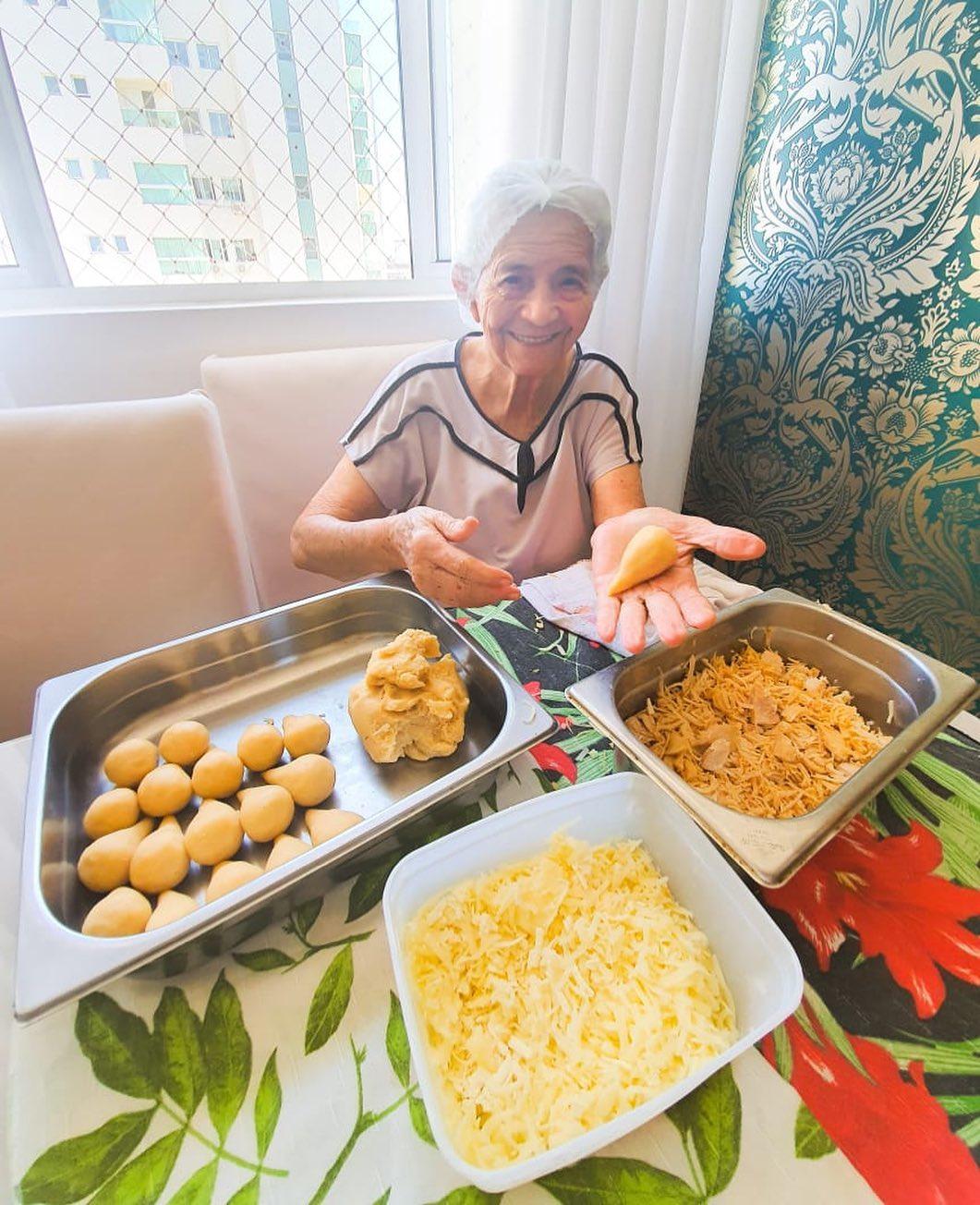 idosa preparando coxinhas sorrindo sentada mesa