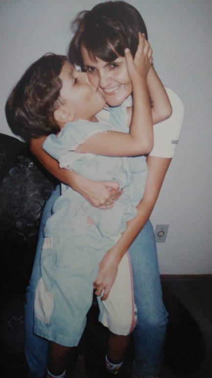 filho pequeno abraçando beijando bochecha mãe