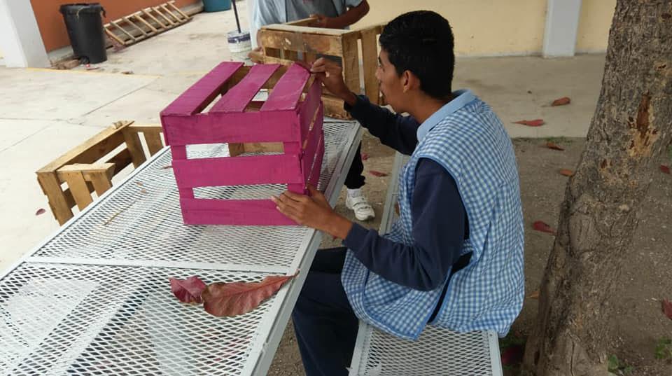 jovem pintando caixote madeira