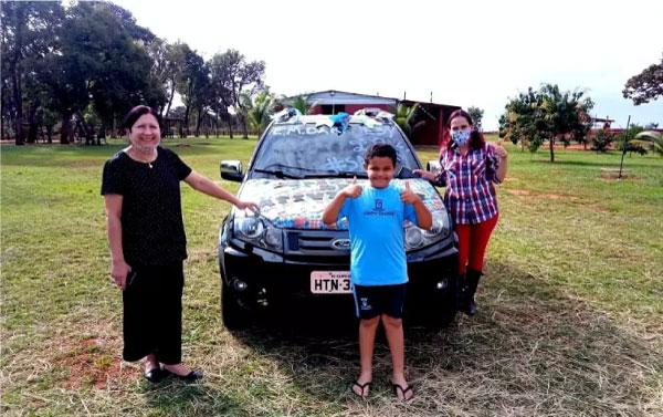 Mulheres e meninos em frente a carro