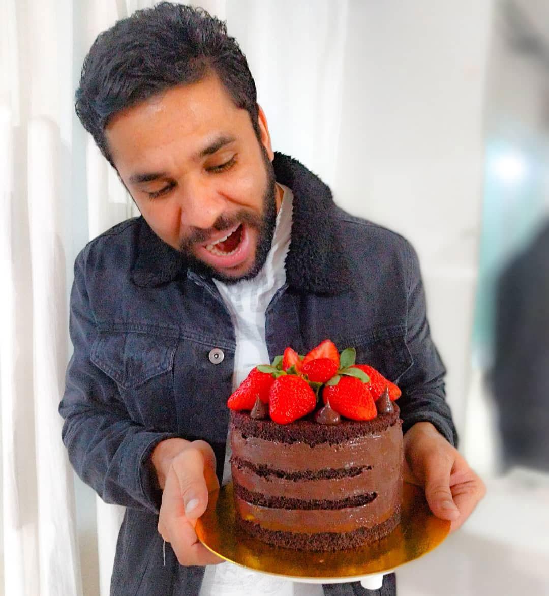 homem segurando bolo chocolate cobertura morango
