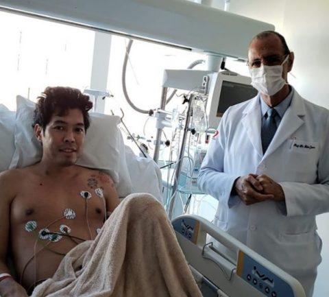 paciente em leito de hospital com médico ao lado e os dois sorrindo para a foto