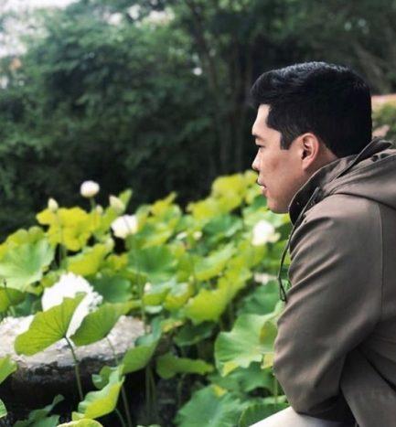 Homem agasalhado olhando para jardim verde