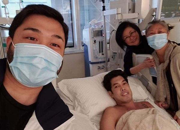 Pessoa internada em leito de hospital com familiares em volta