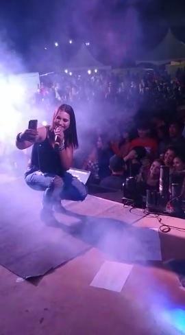 Mulher agachada em palco fazendo selfie com plateia e cantando