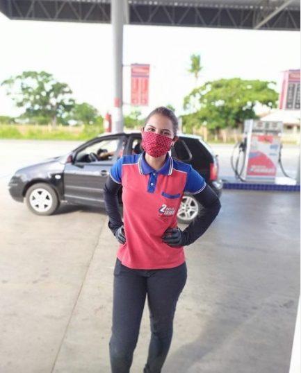 Frentista mulher posando para foto em posto de combustíveis com uniforme de trabalho