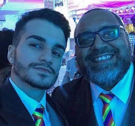 Casal gay: homem negro e homem branco abraçados e sorrindo para a foto