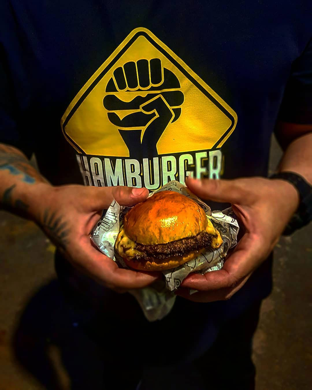 homem segurando hambúrguer