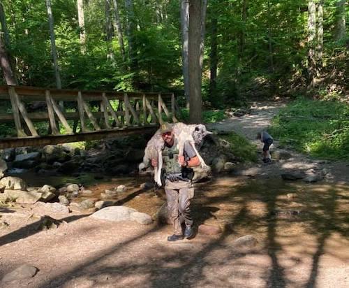 homem atravessando rio com cachorro