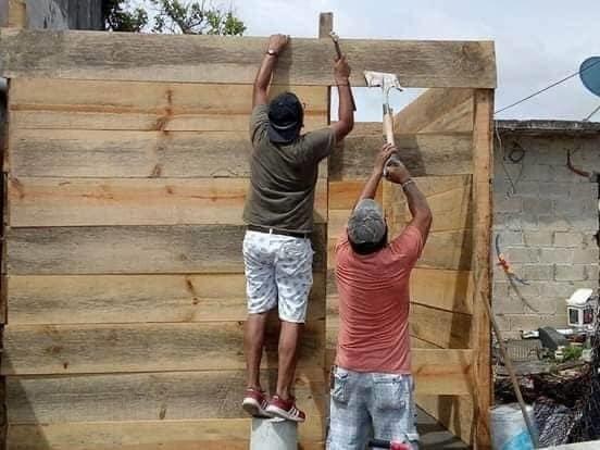 Homens trabalhando em casa de madeira