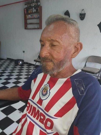 Idoso sentado em salão de beleza com cabelo cortado e barba feita