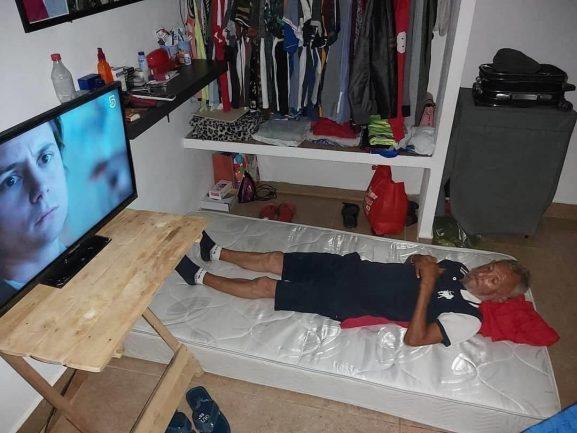 Idoso deitado em colchão na casa nova com TV, banca e guarda-roupa