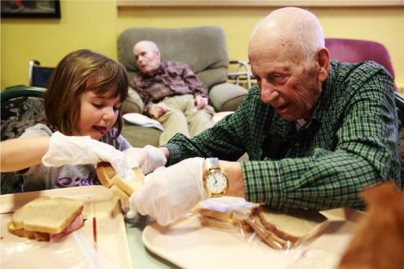 idoso e criança fazendo sanduiche