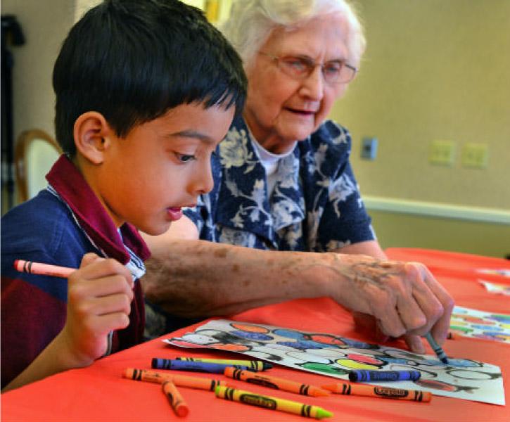 criança e idoso pintando