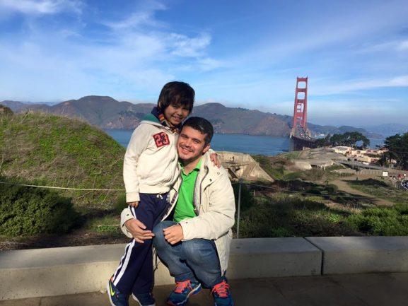 Pai abraçado com filho em paisagem com lago