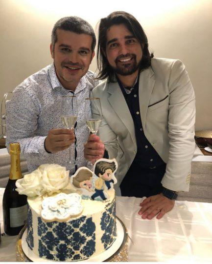 Dois homens com bolo de casamento fazendo brinde