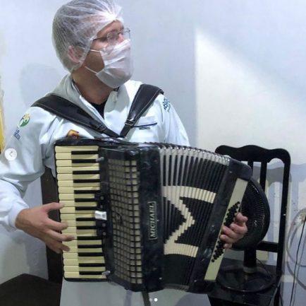 Médico paramentado tocando sanfona dentro de casa de paciente
