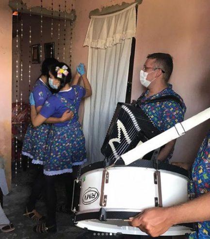 Médico tocando sanfona e profissionais de saúde dançando dentro de casa de paciente