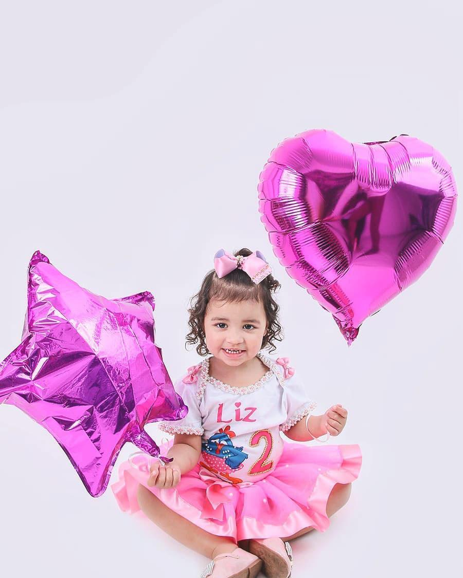 menina segurando balões estrela coração
