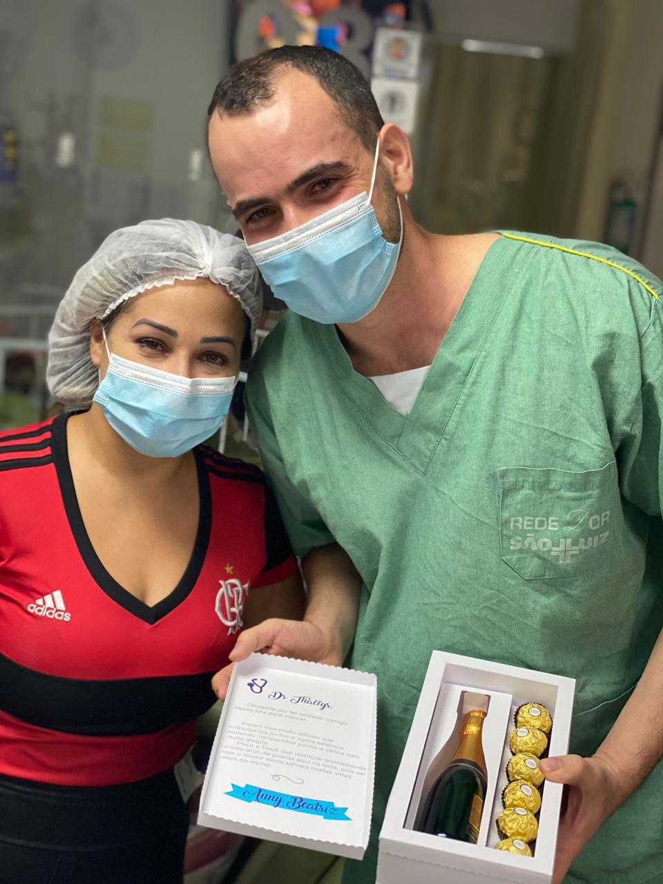 médico ao lado mãe paciente vestindo camiseta flamengo