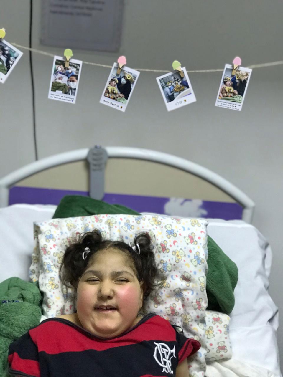 menina usando camiseta flamengo deitada leito uti sorrindo
