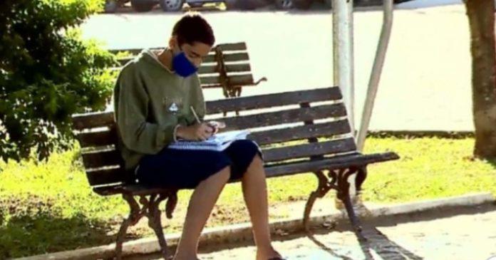 menino estudando banco praça