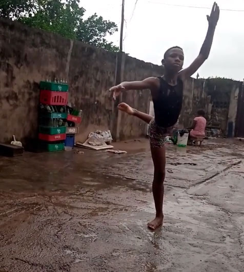 menino faz movimento balé quintal molhado água chuva